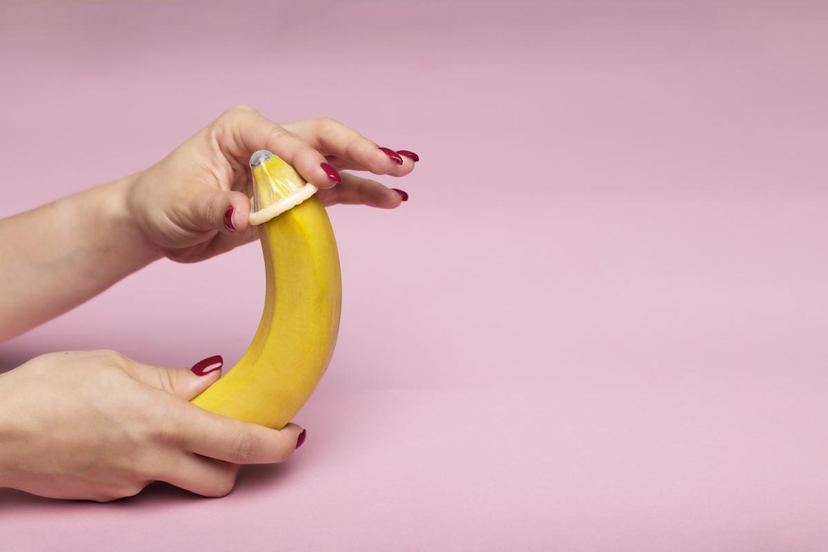hand putting condom on banana